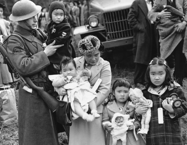 Mrs. Shigeho Kitamoto had no time for tears when she was evacuated along with other Japanese from Bainbridge Island in Washington State, March 30, 1942. She has too busy looking after her four children.  Corporal George Bushy, member of the military guard which supervised the departure of 237 Japanese for California, gave her a hand with the youngest. (Photo by AP Photo)