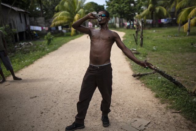 In this February 1, 2018 photo, Angel Ponce takes a swig of rum, in Puerto Lempira, Honduras. Among exotic, tropical vegetation along the Caribbean coast, the Mosquitia region is sprinkled with small fishing villages. (Photo by Rodrigo Abd/AP Photo)