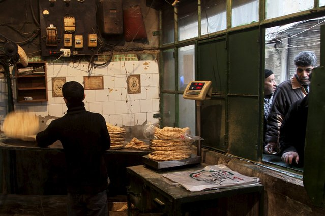 Men queue to buy bread from a bakery in the rebel held al-Shaar neighborhood of Aleppo, Syria, February 10, 2016. (Photo by Abdalrhman Ismail/Reuters)