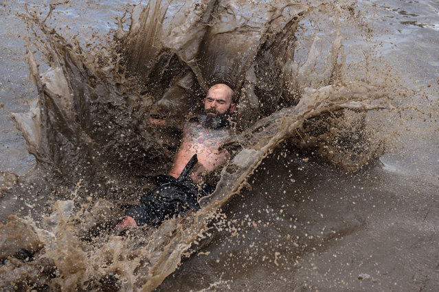 A competitor falls in a muddy pool as they take part in the Tough Guy endurance event near Wolverhampton, central England, on January 27, 2019. (Photo by Oli Scarff/AFP Photo)