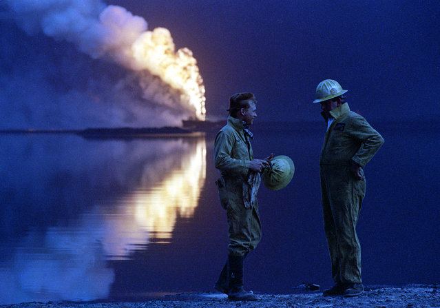 In this July 30, 1991 file photo, oil well firemen from a U.S. company discuss the day's work while a wellhead burns out of control across a lake of crude oil in the Ahmadi oil field, Kuwait. Twenty five years after the first U.S. Marines swept across the border into Kuwait in the 1991 Gulf War, American forces find themselves battling the extremist Islamic State group, born out of al-Qaida, in the splintered territories of Iraq and Syria. Oil prices, which sparked Saddam's invasion of Kuwait, have dropped to under $30 a barrel from more than $100 in just a year and a half. (Photo by John Gapps III/AP Photo)