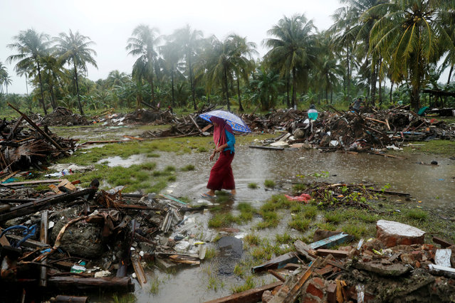 A woman holding an umbrella walks in the rain among debris after a tsunami, in Sumur, Banten province, Indonesia on December 26, 2018. (Photo by Jorge Silva/Reuters)