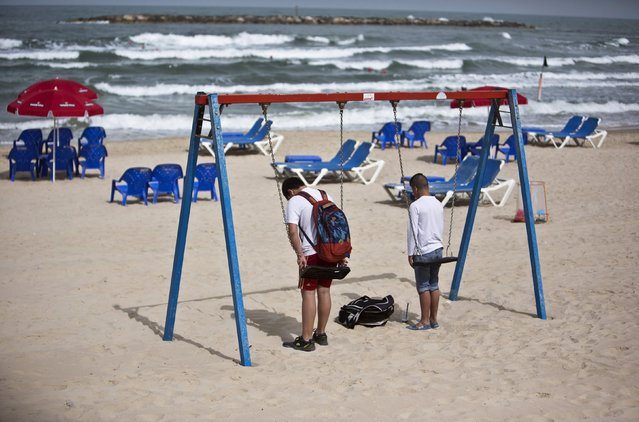 Youths stand still on the beach as a two-minute siren marking Holocaust Remembrance Day is sounded in Tel Aviv April 16, 2015. (Photo by Nir Elias/Reuters)