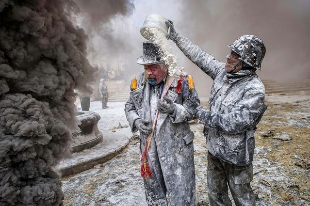 """Revelers take part in the battle of """"Enfarinats"""", a flour fight in celebration of the Els Enfarinats festival in Ibi, Spain, on December 28, 2013. The battle takes place between two groups. A group of married men called """"Els Enfarinats"""" takes control of the village for one day, pronouncing a host of ridiculous laws and fining citizens who break them. Another group called """"La Oposicio"""" then tries to restore order. (Photo by David Ramos/Getty Images)"""