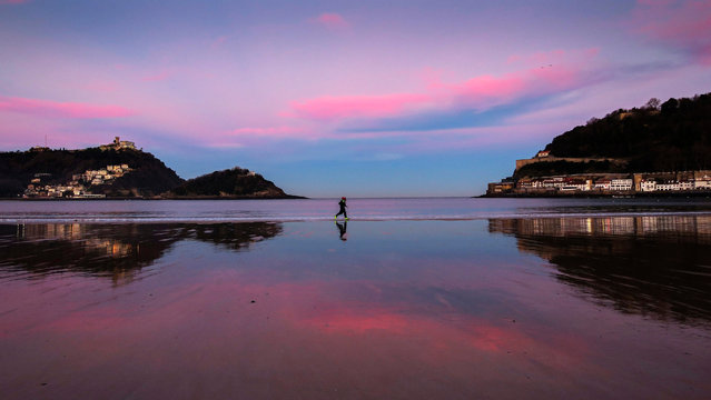 People run during sunrise at La Concha beach in San Sebastian, northern Spain, 28 December 2016. Maximum temperatures will rise up to 17 degrees Celsius in the north of Spain. (Photo by Javier Etxezarreta/EPA)