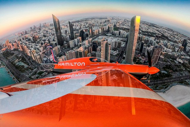 This handout photograph taken and released by Limex Images for Red Bull on February 6, 2019 shows France's Nicolas Ivanoff flying over the skyline prior to the first stage of the Red Bull Air Race World Championship in Abu Dhabi, United Arab Emirates. (Photo by Predrag Vuckovic/AFP Photo)