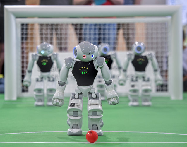 A robot playsa the ball during a soccer match at the RoboCup German Open 2015 in Magdeburg, Germany, Friday, April 24, 2015. Around 200 teams from 14 countries demonstrate the state-of-the-art in robotics with competitions such as soccer, rescue and service robots. (Photo by Jens Meyer/AP Photo)
