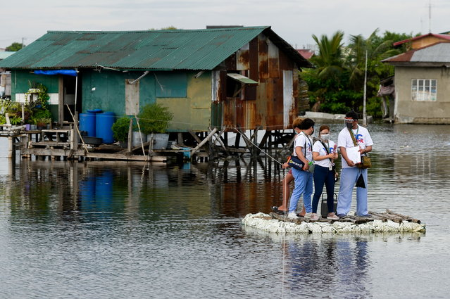 Healthcare workers ride on a makeshift raft during the house to house vaccination of bedridden citizens for the coronavirus disease (COVID-19), in Valenzuela City, Metro Manila, Philippines, July 6, 2021. (Photo by Lisa Marie David/Reuters)