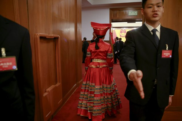 A security officer gestures as an ethnic minority delegate walks past during the opening session of the National People's Congress (NPC) at the Great Hall of the People in Beijing, China, March 5, 2016. (Photo by Kim Kyung-hoon/Reuters)