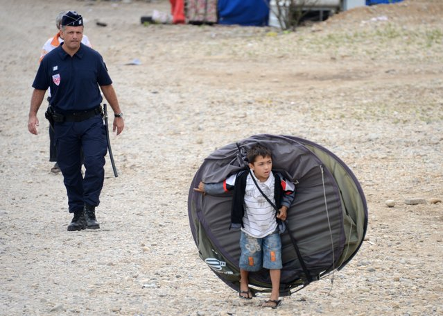 A child from the Roma community leaves a camp after being expelled by French police officers on August 28, 2012, in Saint-Priest, outside Lyon, central-eastern France. (Photo by Philippe Desmazes/AFP Photo)