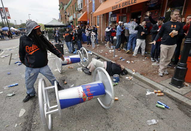 An bar patron lies on the ground after a skirmish with a protester after a rally for Freddie Gray, Saturday, April 25, 2015, in Baltimore. (Photo by Patrick Semansky/AP Photo)