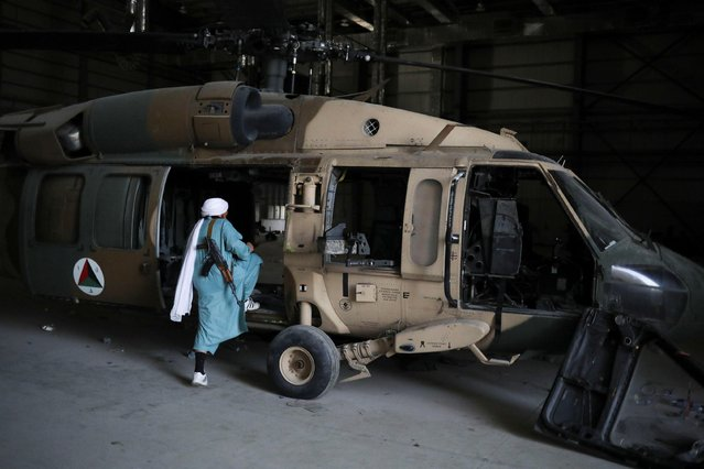 A Taliban soldier enters a helicopter at Bagram Air Base in Parwan, Afghanistan, September 23, 2021. (Photo by WANA via Reuters)