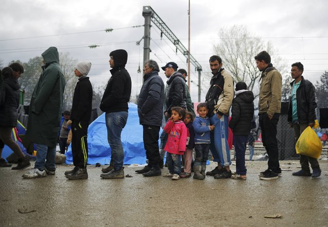 Migrants wait for food in a queue at a makeshift camp on the Greek-Macedonian border near the village of Idomeni, Greece March 10, 2016. (Photo by Stoyan Nenov/Reuters)