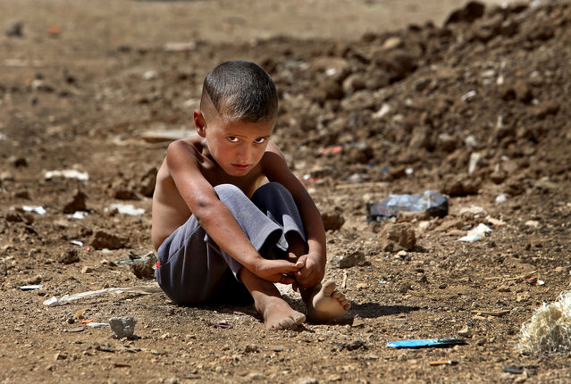In this September 11, 2013 file photo, a Syrian refugee boy sits on the ground at a temporary refugee camp, in the eastern Lebanese town of Al-Faour, Bekaa valley near the Syria-Lebanon border. On Tuesday, January 31, 2017, UNICEF appealed for $3.3 billion this year to help millions of children worldwide facing conflict, malnutrition and other humanitarian emergencies. (Photo by Hussein Malla/AP Photo)