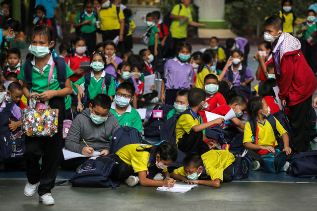 Students wear masks as they wait to be picked up, as classes in over 400 Bangkok schools have been cancelled due to worsening air pollution, at a public school in Bangkok, Thailand, January 30, 2019. (Photo by Athit Perawongmetha/Reuters)