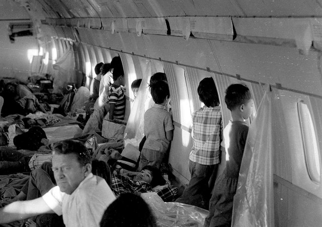 "In this April 1975 file photo, orphans aboard the first ""Operation Babylift"" flight at the end of the Vietnam War look through the windows of World Airways DC-8 jet as it flies them to the United States. (Photo by AP Photo)"