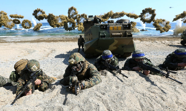 "U.S. Marines, left, and South Korean Marines, wearing blue headbands on their helmets, take positions after landing on the beach during the joint military combined amphibious exercise, called Ssangyong, part of the Key Resolve and Foal Eagle military exercises, in Pohang, South Korea, Saturday, March 12, 2016. North Korea said Saturday its military is ready to pre-emptively attack and ""liberate"" the South in its latest outburst against the annual joint military drills by the United States and South Korea. (Photo by Kim Jun-bum/Yonhap via AP Photo)"