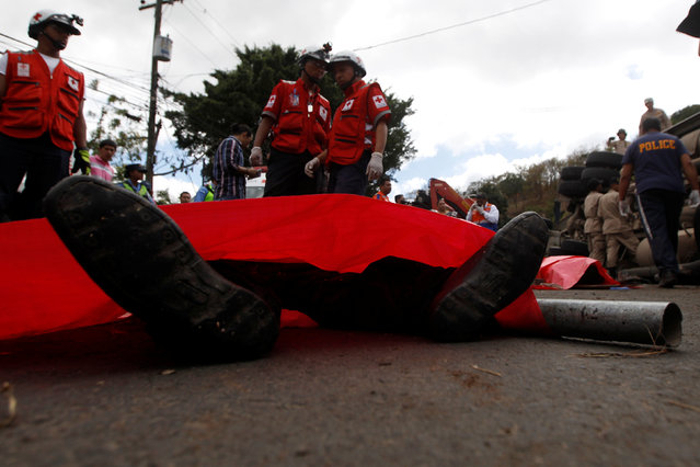 The feet of a dead body are seen next to members of the Red Cross after a crash between a bus and a truck on the outskirts of Tegucigalpa, Honduras, February 5, 2017. (Photo by Jorge Cabrera/Reuters)