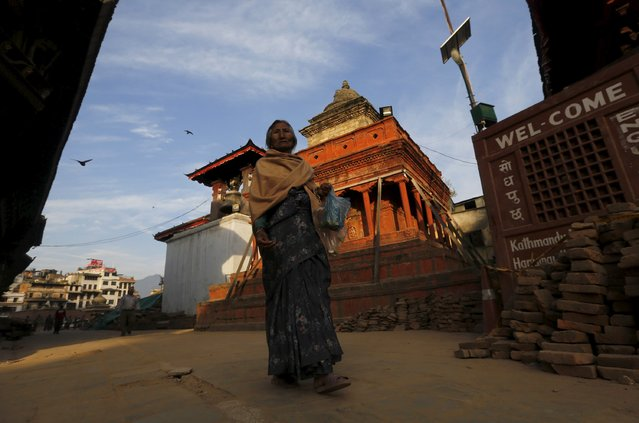 A woman walks past damaged temples at Bashantapur Durbar Square, after the earthquake in Kathmandu, Nepal May 5, 2015. (Photo by Adnan Abidi/Reuters)
