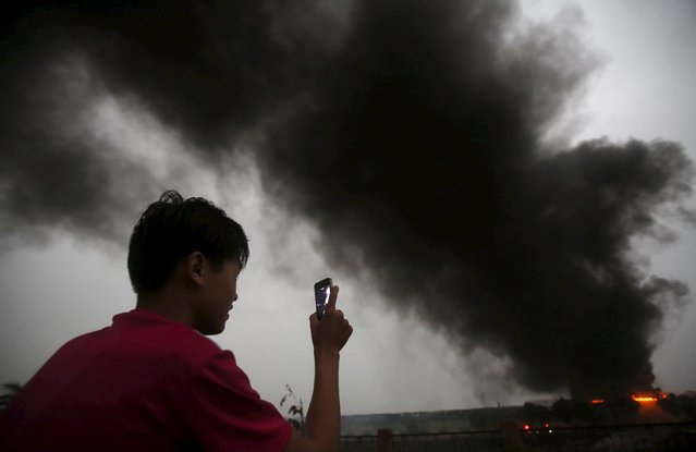 A boy uses a mobile phone to record smoke billowing from a fire at a ceramic factory in Vinh Phuc province, outside Hanoi, Vietnam, March 20, 2016. Investigation is ongoing for the cause of the fire, and no casualties have been reported, according to local media. (Photo by Reuters/Kham)