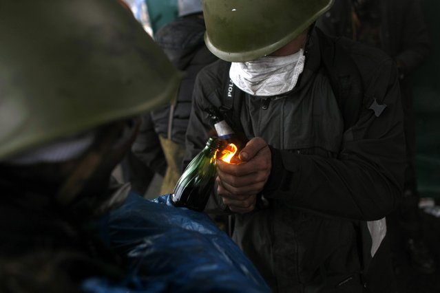Anti-government protesters light petrol bombs on the outskirts of Independence Square in Kiev, Ukraine, Thursday, February 20, 2014. (Photo by Marko Drobnjakovic/AP Photo)