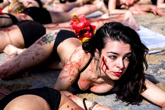 """A woman spits red paint as if it is blood protesting against bullfights in Madrid, Spain on March 27, 2016. Anti-bullfighting protesters have turn the iconic square of """"Puerta del Sol"""" into a bullring. Protesters, almost naked covered with red paint as if it was blood, have demanded the abolition of bullfights under the slogan """"The bull suffers!"""". (Photo by Marcos del Mazo/Pacific Press)"""