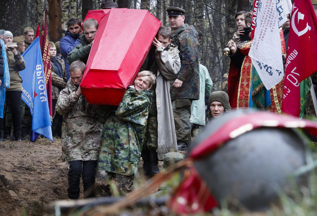 Members of volunteer search teams carry coffins with the remains of Soviet soldiers killed during World War II, during a reburial ceremony at the Sinyavino Heights memorial near the village of Sinyavino, 50 km (31 miles) east of St. Petersburg, Russia, Tuesday, May 7, 2019. Hundreds of people came to a World War II battleground outside St. Petersburg to bury the remains of 714 Soviet soldiers recovered by volunteer search teams. Forty one crimson coffins containing skulls and bones were solemnly buried at the Sinyavino Heights memorial as Russian war songs played and an honor guard fired a salute. (Photo by Dmitri Lovetsky/AP Photo)