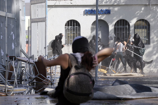 Protesters recover after being hit by a jet of water from a police operated water cannon at the University of Santiago, during clashes between students and police, in Santiago, Chile, Thursday, May 14, 2015. (Photo by Luis Hidalgo/AP Photo)