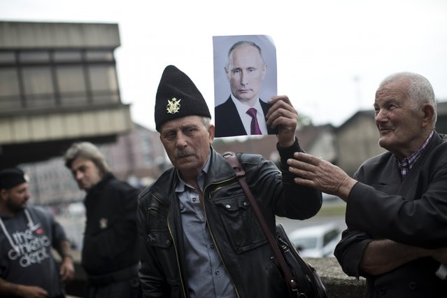 A supporter of Gen. Draza Mihajlovic, a World War II royalist guerrilla commander, holds a photo of Vladimir Putin, the Russian president, as he stands in front of the Higher Court in Belgrade, Serbia, Thursday, May 14, 2015. A Belgrade court on Thursday quashed the treason conviction of Mihailovic for his collaboration with Nazis during World War II. (Photo by Marko Drobnjakovic/AP Photo)