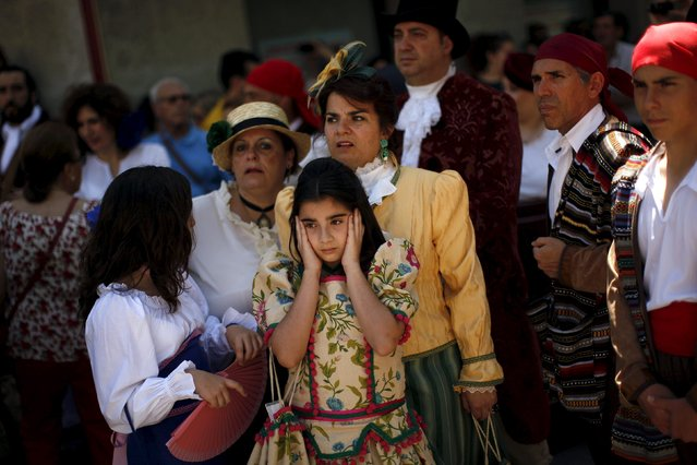 "A girl, wearing a traditional costume, covers her ears as members of a historical battle re-enactment group dressed in early nineteenth century French army uniforms (not pictured) fire their weapons during a Spanish Independence War battle re-enactment during the third edition of ""Ronda Romantica"" (Romantic Ronda) in Ronda, southern Spain, May 16, 2015. (Photo by Jon Nazca/Reuters)"