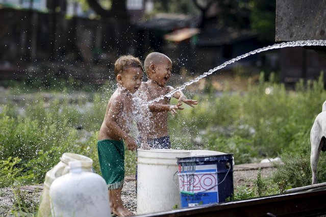 Children play with water at a train station in Yangon May 11, 2015. (Photo by Soe Zeya Tun/Reuters)