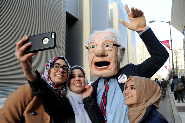 Wearing an oversized Bernie head, Dennis Meserole, poses for selfie with students in line to see Democratic presidential hopeful Bernie Sanders on Wednesday, April 6, 2016, at Temple University in Philadelphia. (Photo by Tom Gralish/The Philadelphia Inquirer via AP Photo)
