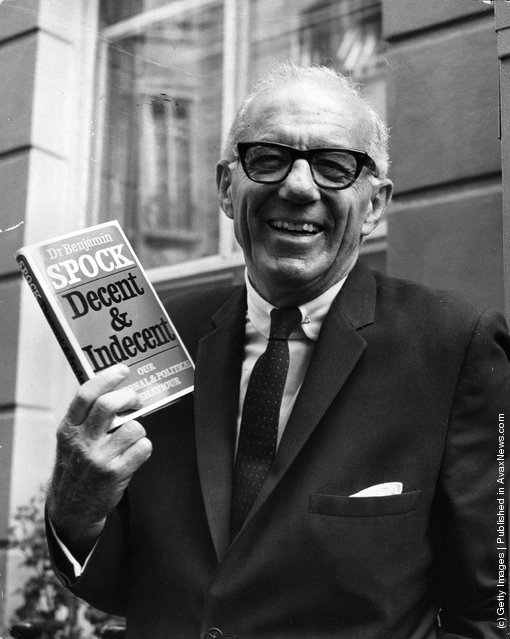 Dr Benjamin Spock  noted for his ideas on child-rearing, on a visit to Britain, holds up a copy of his book, Decent & Indecent