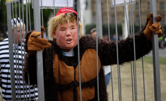 Man in a mask stands in a cage as people start to gather to demonstrate against the state visit of President Donald Trump in Parliament Square, central London, Tuesday, June 4, 2019. Trump will turn from pageantry to policy Tuesday as he joins British Prime Minister Theresa May for a day of talks likely to highlight fresh uncertainty in the allies' storied relationship. (Photo by Matt Dunham/AP Photo)