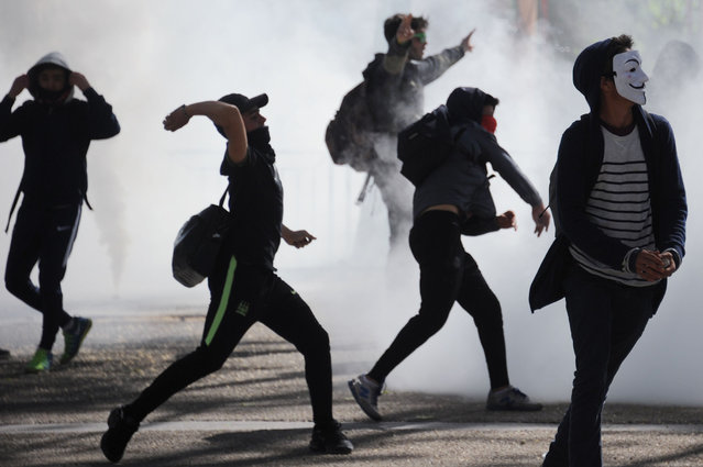 Students throw projectiles at riot police on April 14, 2016 in Montpellier, southern France, during a demonstration against the government's planned labour reform. (Photo by Sylvain Thomas/AFP Photo)