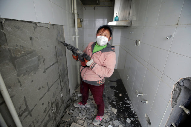 """Deng Qiyan, 47, a mother of three and a decoration worker at contraction sites, poses for a photograph at an apartment building under construction in Beijing, China, February 22, 2017. """"Sometimes (gender inequality) happens. But we cannot do anything about that. After all, you have to digest all those unhappy things and carry on"""", Qiyan said. (Photo by Jason Lee/Reuters)"""