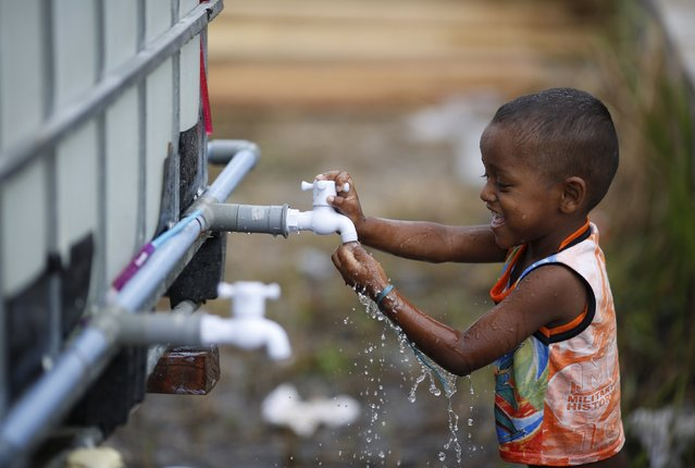 A young Rohingya migrant, who arrived recently by boat, plays with a water tap at a temporary shelter in Kuala Langsa, in Indonesia's Aceh Province May 25, 2015. Malaysia's police chief said on Monday that 139 graves believed to contain the remains of migrants were found near the country's border with Thailand, and that some graves contained more than one body. (Photo by Nyimas Laula/Reuters)