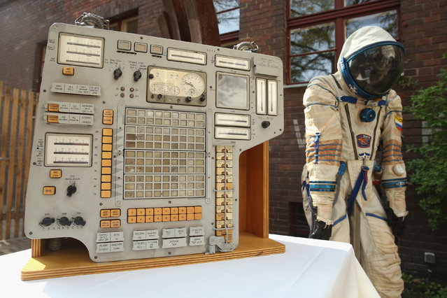 An original instrument panel from the Vozvrashchayemyi Apparat (VA) former Soviet space capsule and a Sokol KV2 spacesuit stand on display during a press preview before the auction of the capsule on April 3, 2014 in Berlin, Germany. The capsule, which could carry three astronauts, served on two Cosmos space missions in the late 1970s. It will be on display in Berlin from April 4–7 and is scheduled to be sold at auction in Brussels on May 7. (Photo by Sean Gallup/Getty Images)