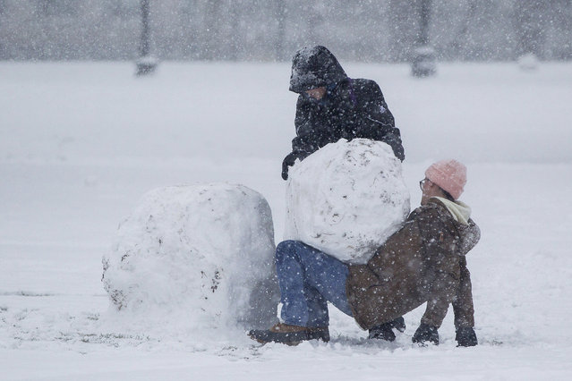 Two women work to build a snowman on the Boston Common walk through the Boston Common as Winter Storm Stella bears down on March 14, 2017 in Boston, Massachussets. (Photo by Scott Eisen/Getty Images)