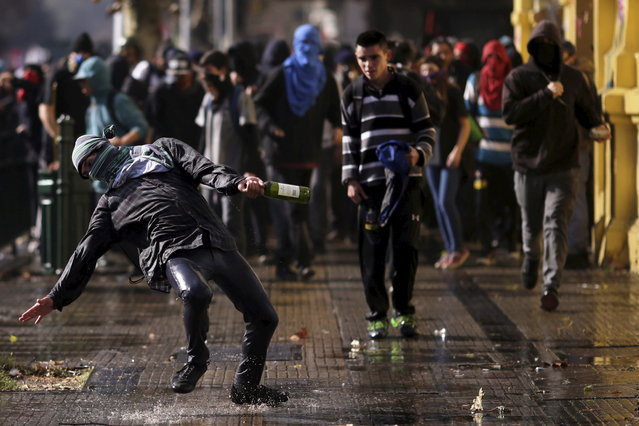 A protester, with a bottle, runs towards police during a demonstration to demand changes in the Chilean education system in Santiago, Chile June 25, 2015. (Photo by Ueslei Marcelino/Reuters)