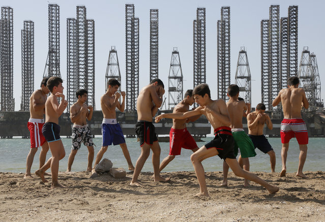 Teenagers belonging to a kickboxing school attend a training session at a beach on the Caspian Sea with Soviet era oil platforms in the background, Baku, Azerbaijan, Saturday, June 27, 2015. The 2015 European Games are being held in Baku until June 28. (Photo by Dmitry Lovetsky/AP Photo)