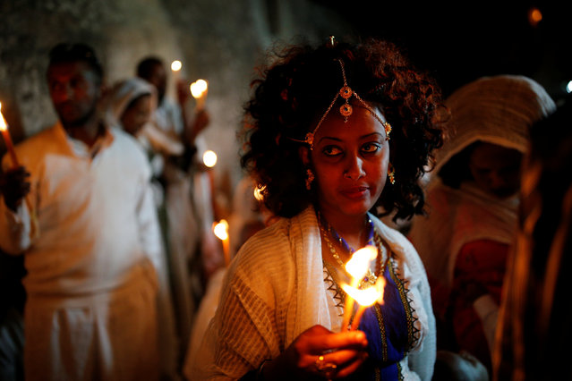 An Ethiopian Orthodox worshipper holds candles during the Holy Fire ceremony at the Ethiopian section of the Church of the Holy Sepulchre in Jerusalem's Old City April 30, 2016. (Photo by Amir Cohen/Reuters)