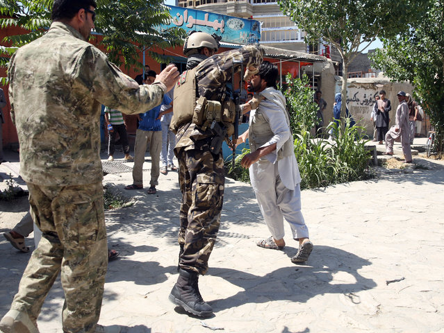 An Afghan soldier beats a man at the site of a suicide car bomb attack on a NATO convoy in Kabul, Afghanistan, Tuesday, June 30, 2015. An eyewitness said the man was later released. (Photo by Massoud Hossaini/AP Photo)