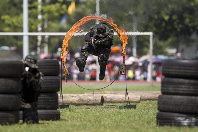 A People's Liberation Army (PLA) commando jumps through a fire hoop part of an exercise during an open day event at the Ngong Shuen Chau Barracks, the PLA navy base in the territory, in Hong Kong, China, 01 July 2015. Thousands of visitors attended the PLA open day yesterday and today to mark the 16th anniversary of the handover from British rule. (Photo by Jerome Favre/EPA)