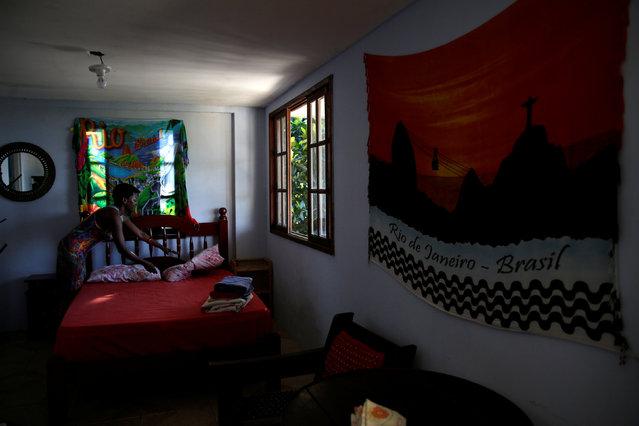 Solange, a worker at Pousada Favelinha (Little favela) hostel, prepares a room in Pereira da Silva favela, in Rio de Janeiro, Brazil, April 21, 2016. (Photo by Pilar Olivares/Reuters)