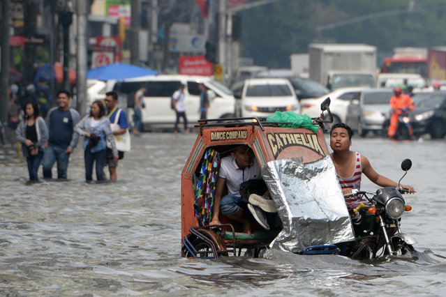 A commuter holding his shoes rides on a tricyle through a flooded street, caused by a heavy downpour brought about by the southwest moonson, in Manila on August 2, 2019. (Photo by Ted Aljibe/AFP Photo)