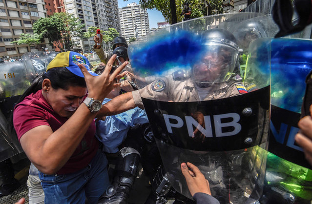 Venezuela' s opposition activists clash with riot police agents during a protest against Nicolas Maduro' s government in Caracas on April 4, 2017. Protesters clashed with police in Venezuela Tuesday as the opposition mobilized against moves to tighten President Nicolas Maduro' s grip on power. Protesters hurled stones at riot police who fired tear gas as they blocked the demonstrators from advancing through central Caracas, where pro- government activists were also planning to march. (Photo by Juan Barreto/AFP Photo)