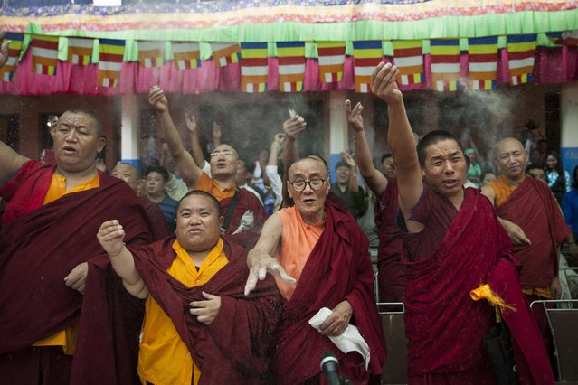 Exiled Tibetan monks toss barley in the air at a gathering to celebrate their spiritual leader, the Dalai Lama's, 80th birthday in New Delhi, India, Monday, July 6, 2015. The Dalai Lama was born on July 6 according to the Gregorian calendar, in the eastern Tibetan region of Amdo in 1935. (Photo by Tsering Topgyal/AP Photo)
