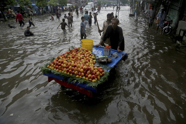 A Pakistani vendor pushes his cart, while youngster play in a flooded street after a heavy rainfall in Lahore, Pakistan, Saturday, July 20, 2019. (Photo by K.M. Chaudary/AP Photo)
