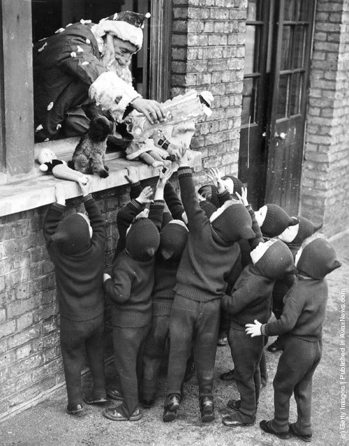 1938: Father Christmas hands out presents to children at the Aid And Adoption Society home at Leytonstone